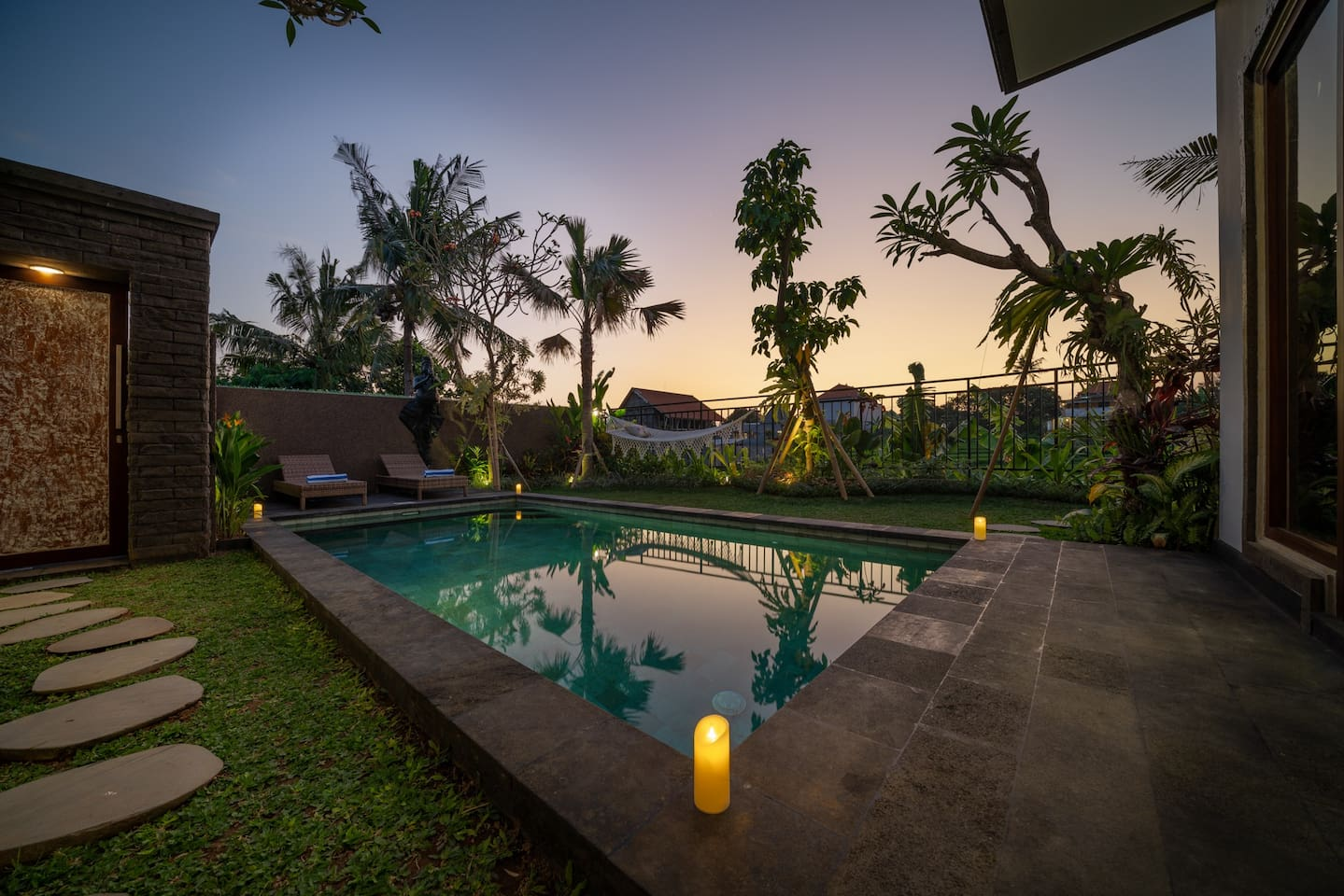 Sunset living-room view of pool, garden and rice fields