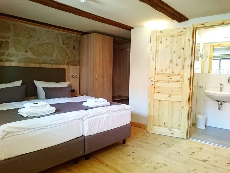 Schlafzimmer mit Doppelbett und Bad