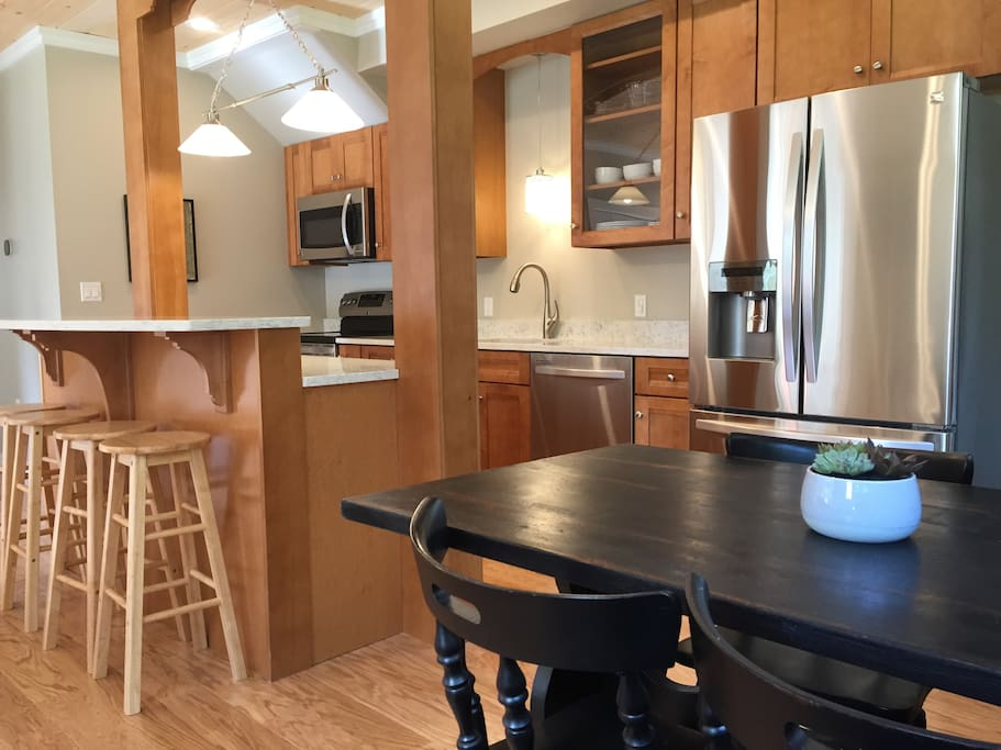 Modern, fully equipped kitchen with eat at bar and dining room table.