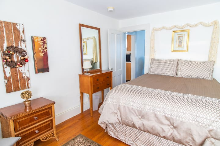 """Bedroom 2 is the """"Princess"""" room, has a comfy queen size bed, as well as a sitting area and a full size mirror on the wall by the closet."""