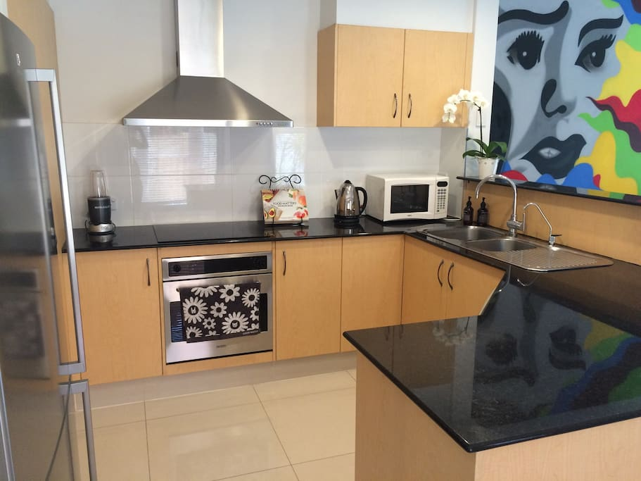 This kitchen is fully equipped including microwave, oven, Nutri bullet, rice cooker, fry pans, steamer, salad spinner, etc with stunning views of a most luscious leafy tree lined park.