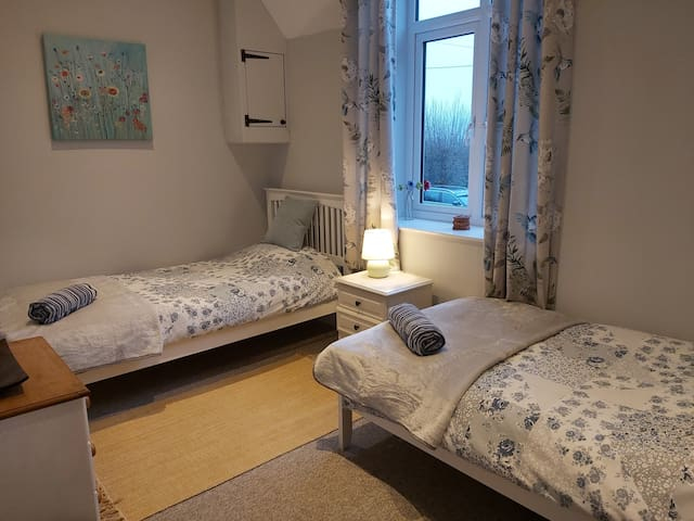 The delightful twin bedroom has far reaching views over the fields to the Cotswold hills. A travel cot and bed safety rail are available upon request.