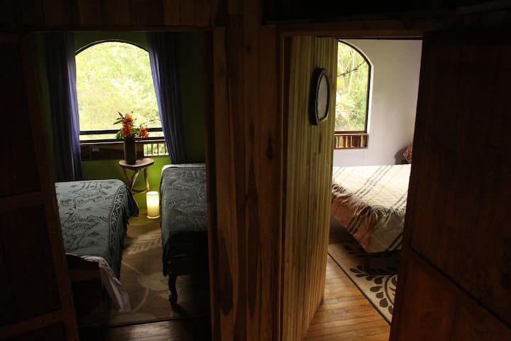Entrance to two rooms: one with a double bed and private bathroom and another with two twin beds.