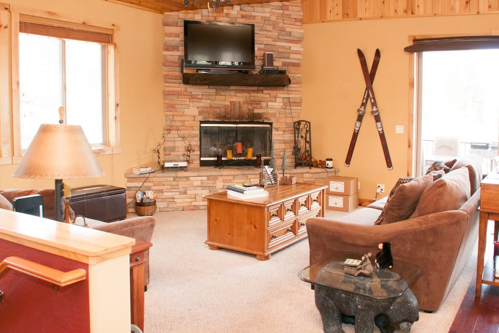 living room with flat screen tv, gas and wood burning fireplace, and sofa sleeper