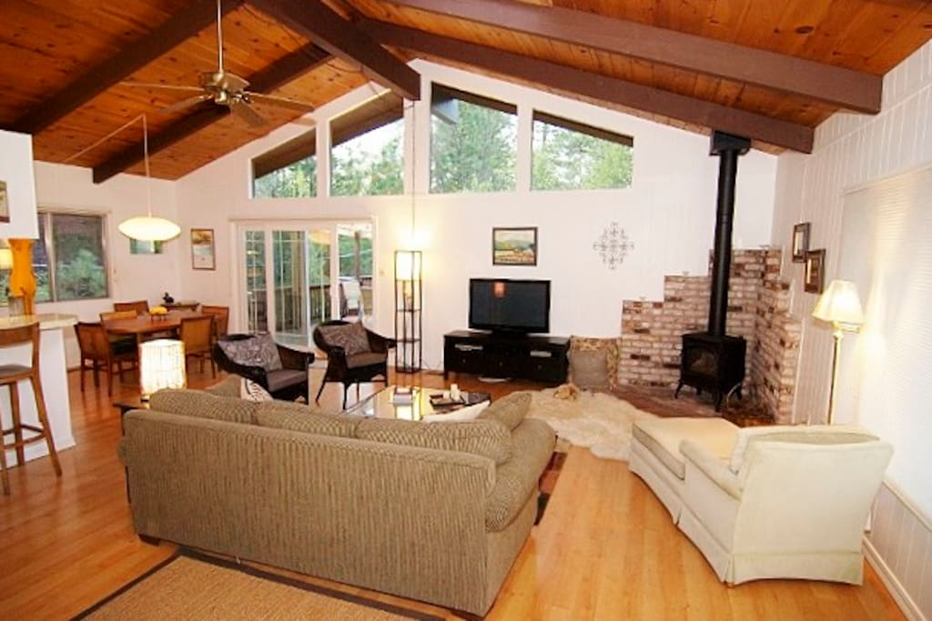 The main room.  View as you enter front door.  Notice the wonderful high windows framing the trees, cozy propane log fireplace and flat screen tv..
