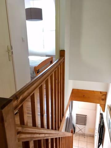 La vue depuis le haut de l'escalier: à l'étage, un dégagement avec 2 lits de 90 superposés masqués par un rideau ainsi que des placards pour le rangements des affaires, la salle bain et la chambre parentale séparée...