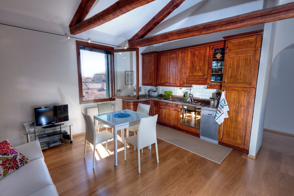 The apartment has oak flooring and exposed beams, with modern furniture