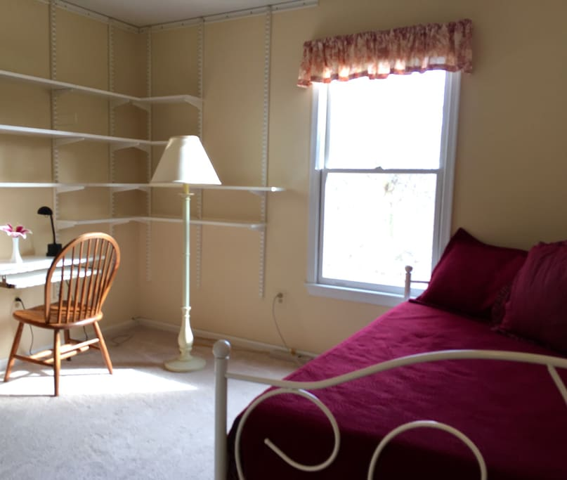 This small, cozy bedroom comes with one floor lamp,  a desk for a laptop or tablet with slide out keyboard tray, a small closet, wall shelves, and a compact table with matching shelves for storing smaller items. One window provides natural light and a view of the birch tree outside.