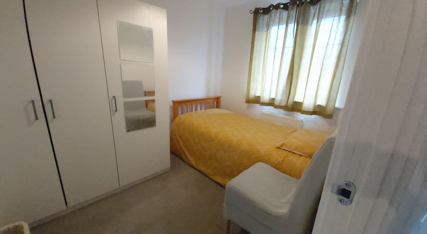 Room with comfortable single bed and wardrobe