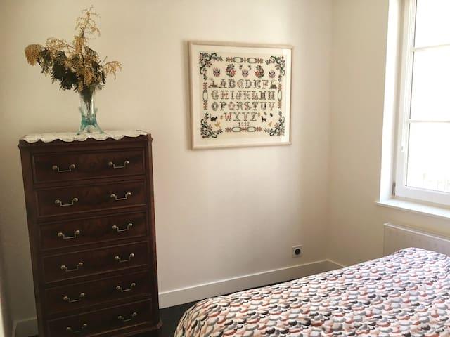Chambre à coucher : lit double, table de chevet, réveil, lampe de chevet, commode, volets et stores occultants