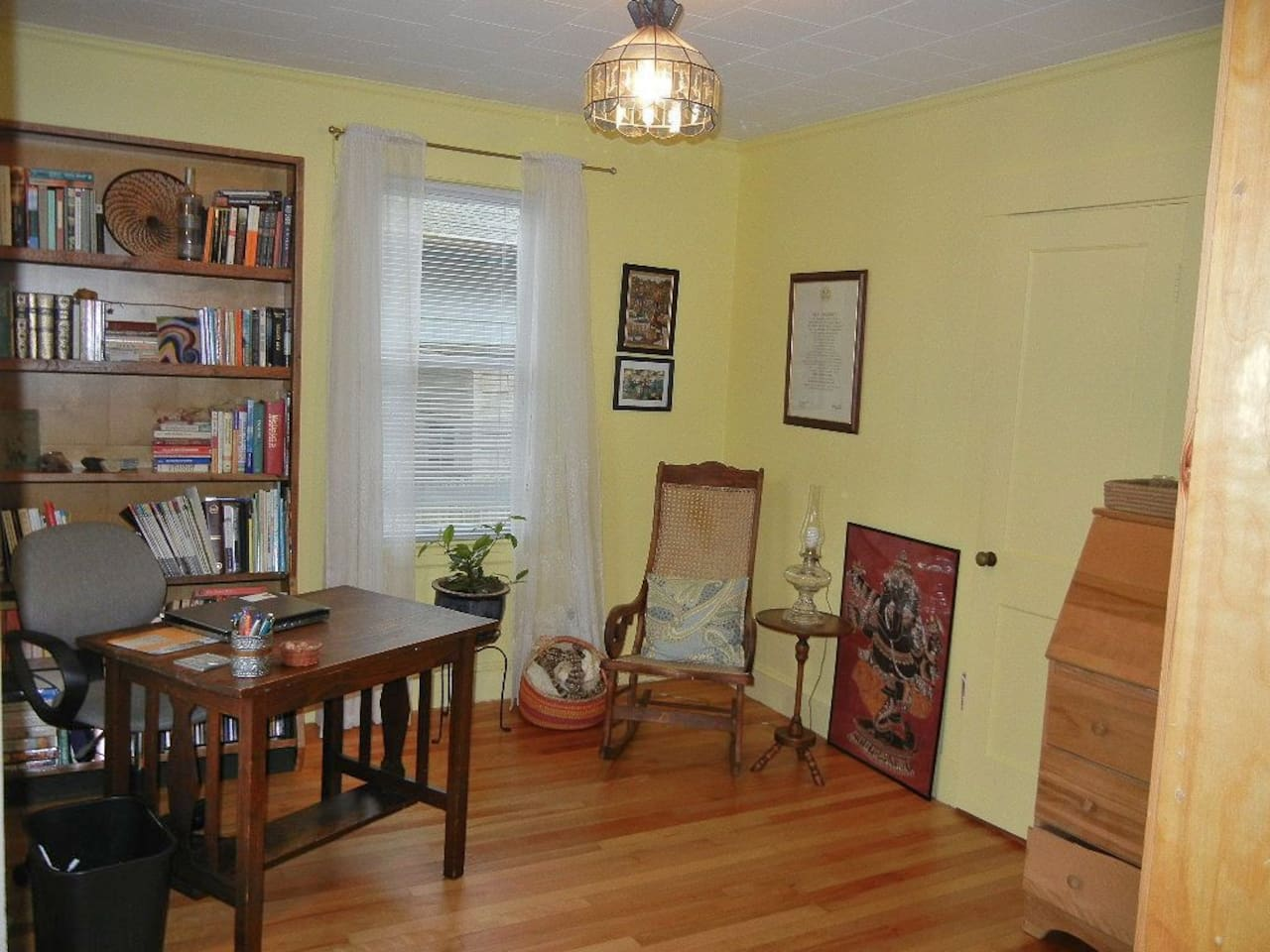 Our library with antique library table and recycled shelves from LL Bean -- a cozy, quasi-office space if you need to do work while here. Also we just installed a new wood pellet stove here (so rocking chair is gone).