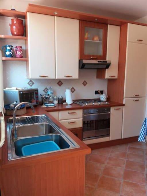 Cucina con lavastoviglie forno e stoviglieria