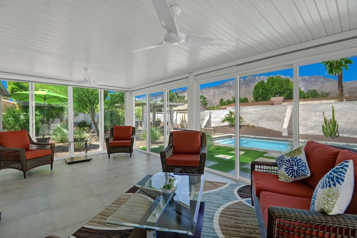 The sunroom offers incredible views of the pool with a majestic mountain backdrop.