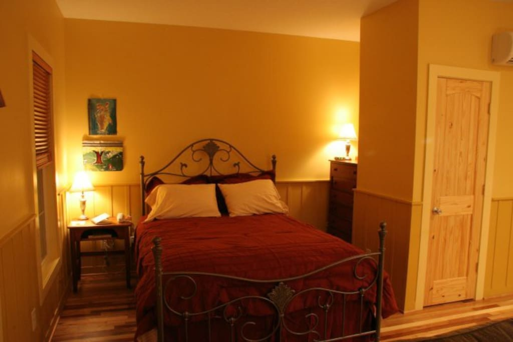 The sleeping area  features a comfortable queen size bed, nightstand, and chest.