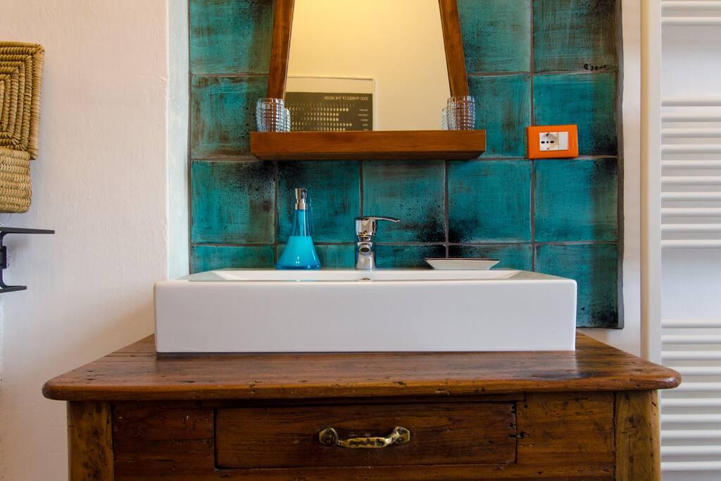Il bagno è esclusivo, interno alla stanza e dispone di doccia in cristallo e ceramiche realizzate a mano da un'artista emiliana (per gli ospiti shampoo, sapone e phon a disposizione)
