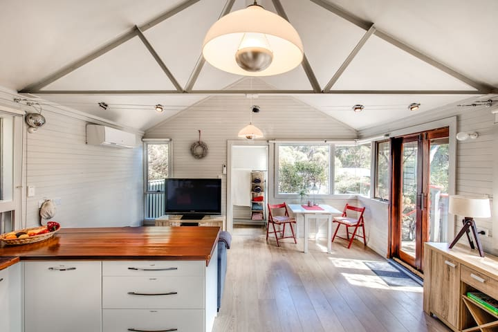 High cathedral ceilings make the cosy cottage feel spacious. Photo: Quentin Chester