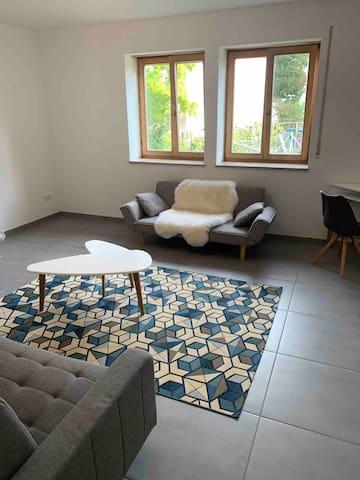 Wohnzimmer mit Blick in den Garten. Kleines Sofa mit Schlaffunktion (1 kleinere Person), neuer Couchtisch, Eckschreibtisch mit Stuhl