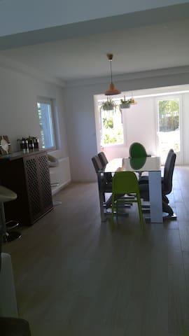 salle à mangé ouverte sur la cuisine et le salon, la porte donne sur le jardin et la piscine