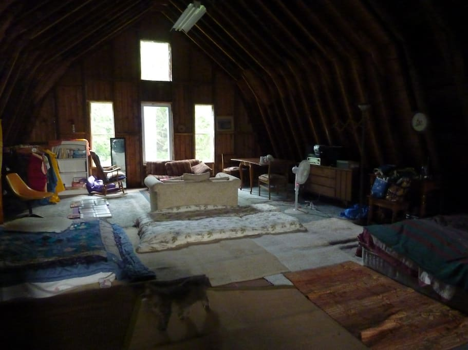 Inside the barn, a futon on either side and a sitting area near the windows. A table and several dressers are nearby. Tune in the radio for some music or talk shows.