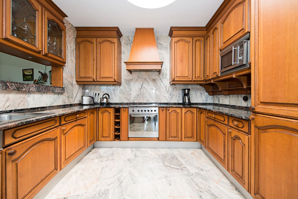 Fully stocked kitchen with coffee maker, oven, microwave and dish washer