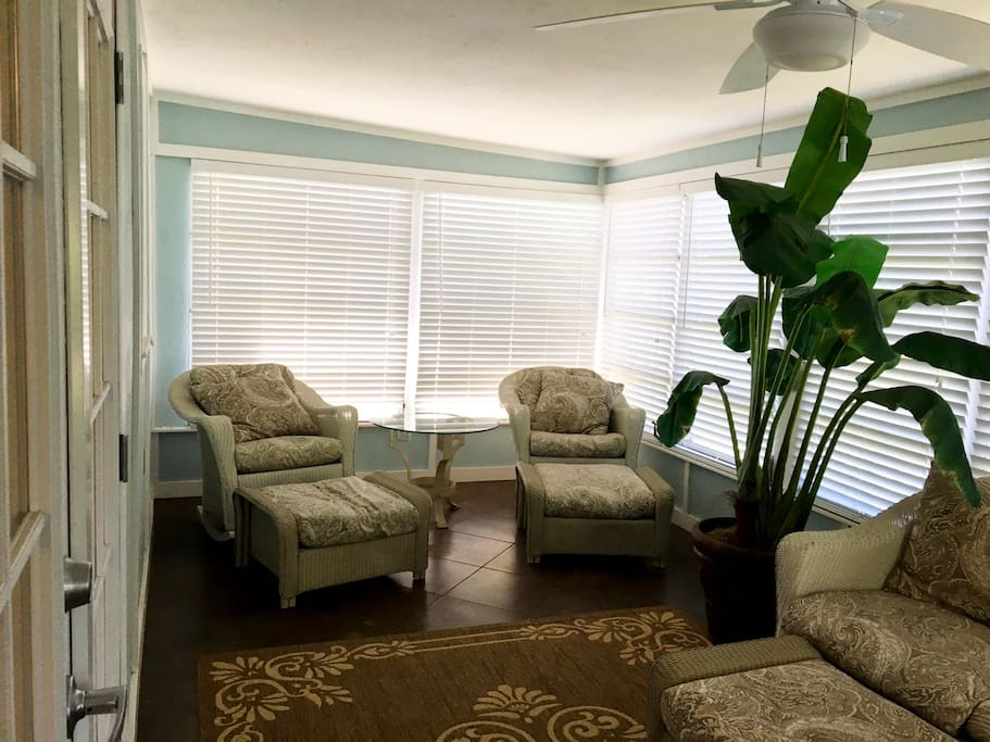 Florida room has seating for five. Blinds can be adjusted and windows can be opened