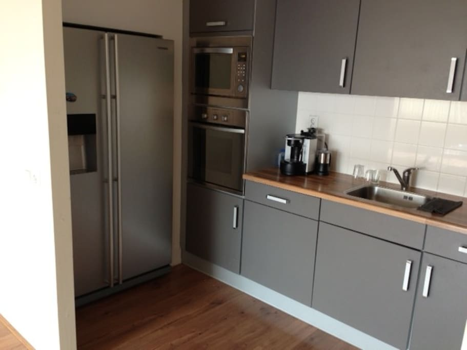 Kitchen with refrigerator, oven and microwave.