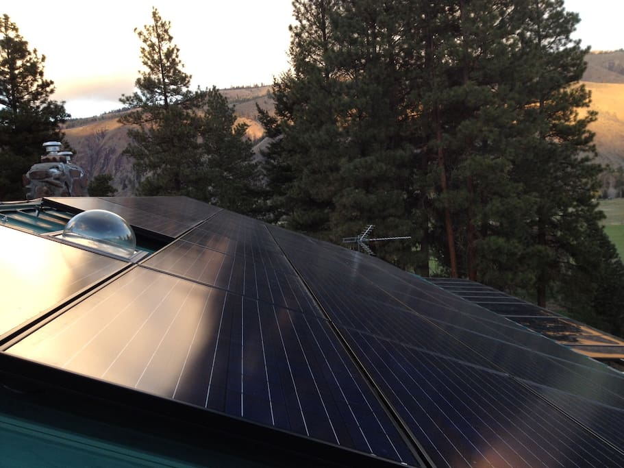 Solar panels on the roof top generate power for the lodge.  The hill across the river shine at sunset.