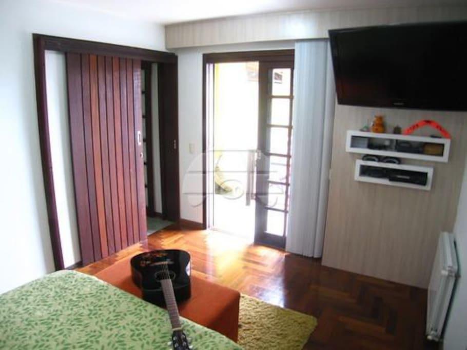Quarto suite com cama de casal com porta para sacada com jardim.