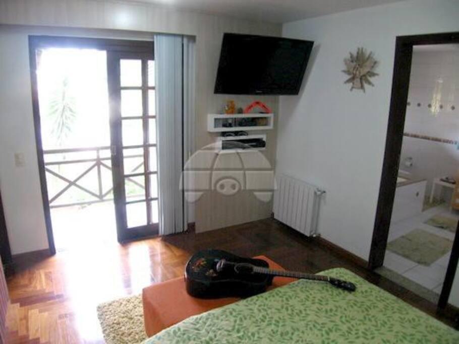 Quarto suite com cama de casal com porta para sacada para o jardim