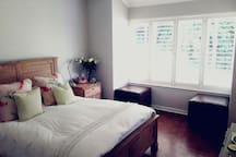 Main bedroom with extra-length queen bed, beautiful bay window and an en-suite bathroom.