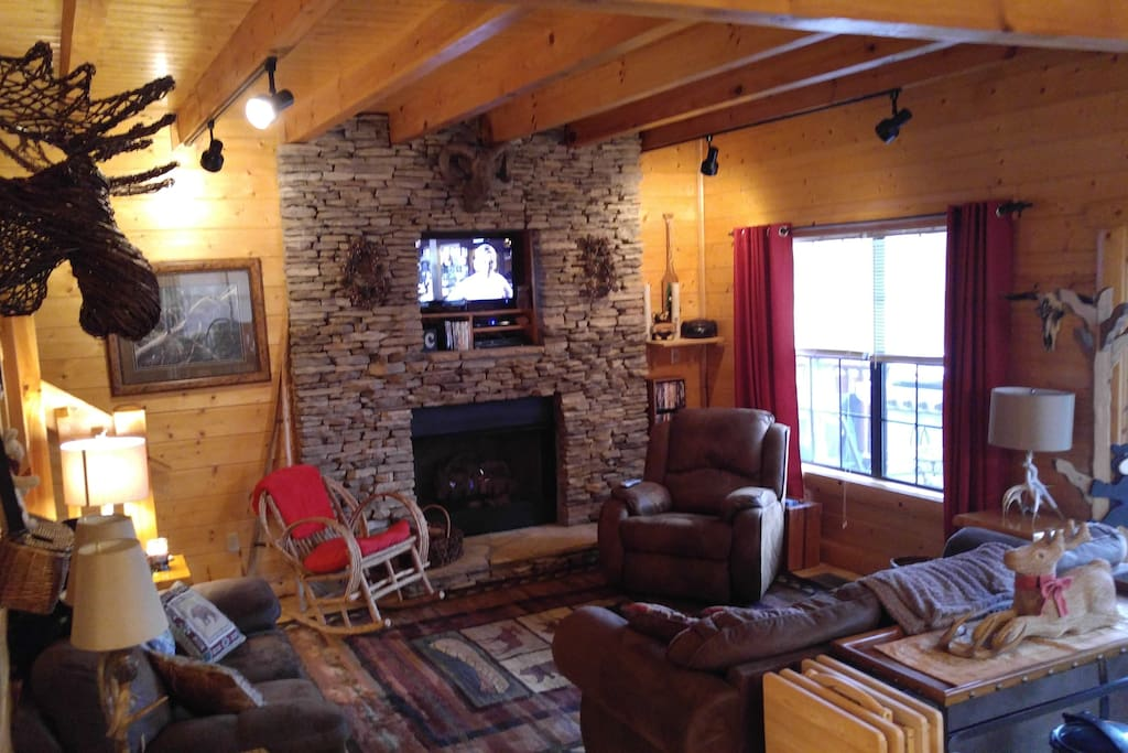 Large open area with floor to ceiling fireplace, living area with sofa, love and chairs for relaxing.