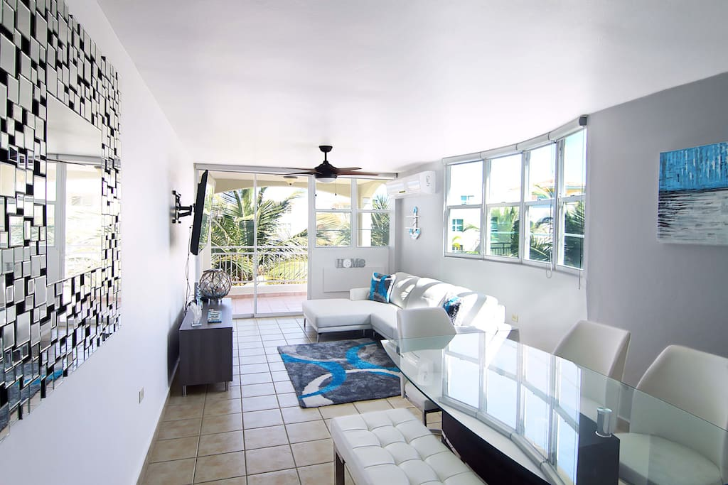 "Living Area facing the Swimming Pool and the Beach. Equipped with: White leather couch, 50"" HDTV, Dinning Table for 6"