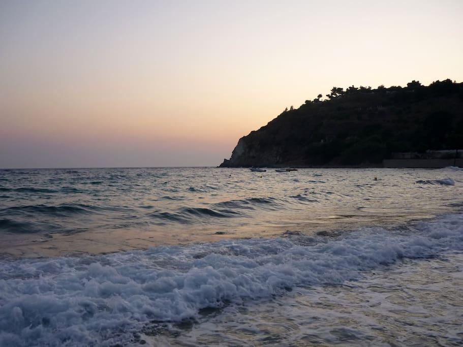 La spiaggia sulla baia. Il profilo del capo si staglia contro il cielo rosato al tramonto
