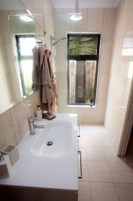The shower area is easily accessible and has a rain shower and a hand held nozzle