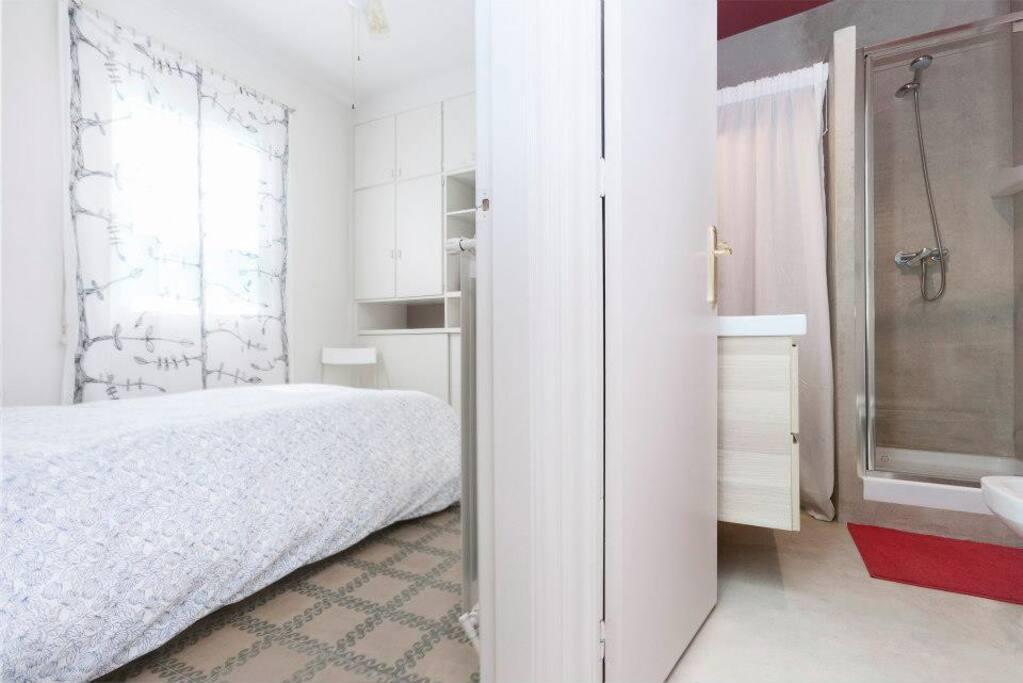 Las camas unidas formando una queen size y puede verse el diseño del suelo típico catalán y el baño junto a la habitación