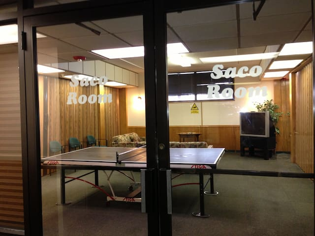 lounge area in bottom floor of building, front desk has ping pong equipment