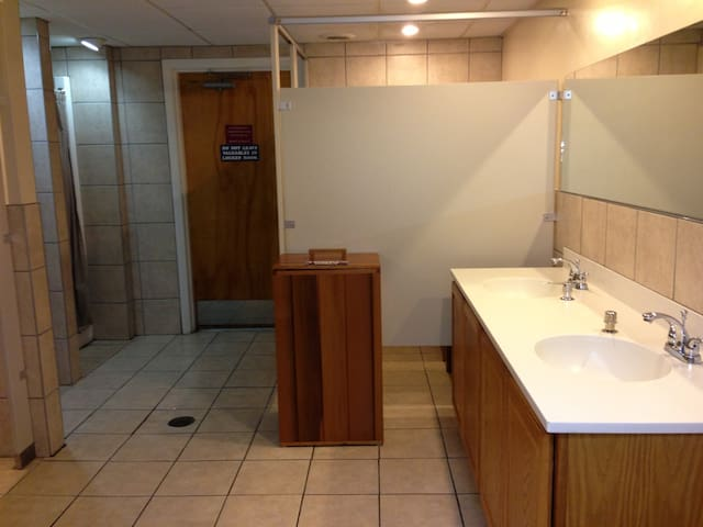 Changing room in bottom floor of building with shower, toliet and changing area