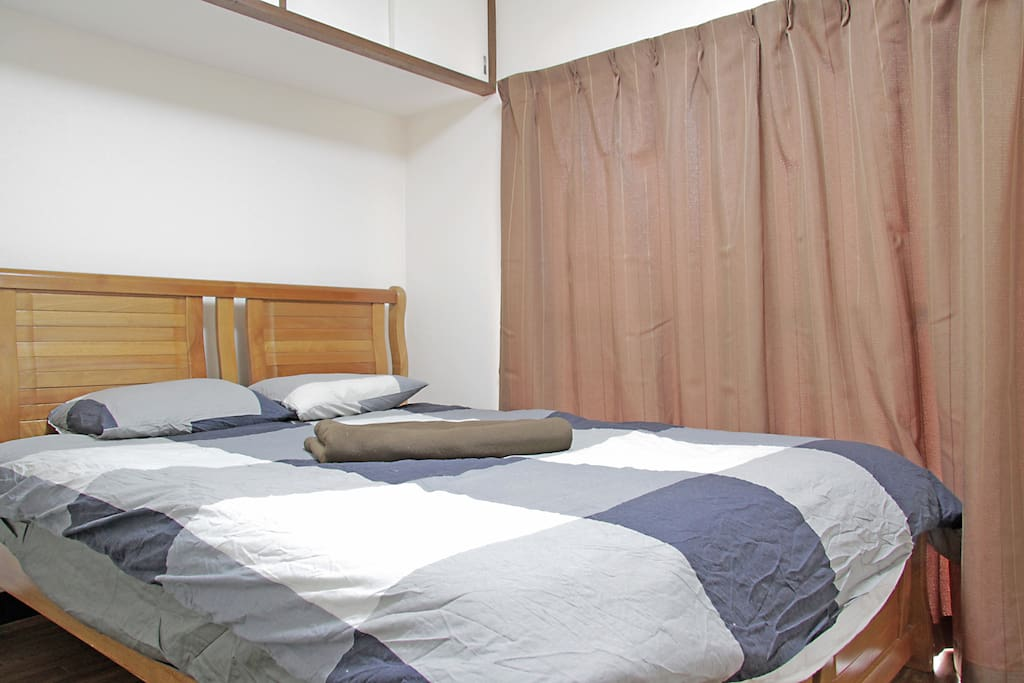 Room with a double bed with the curtains closed