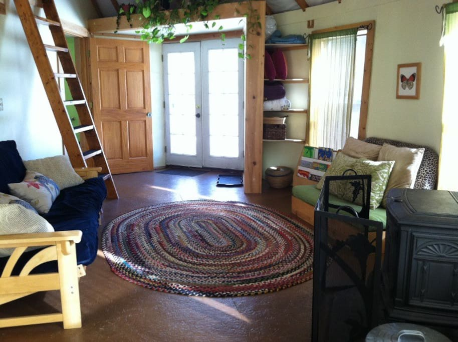 Living Room with full size futon couch/bed and White Lotus childs bed. Thermostat-controlled wood pellet stove keeps t he yurt cozy on cold nights. Pellets provided.
