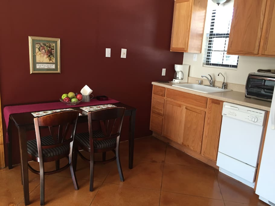 Kitchenette with full size refrigerator and freezer, large sink, dishwasher, microwave, large toaster oven, coffee maker, dishes, and table for two.