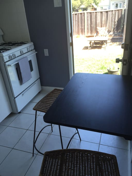 Foldable kitchen table and gas stove. Outdoor seating area and large backyard.