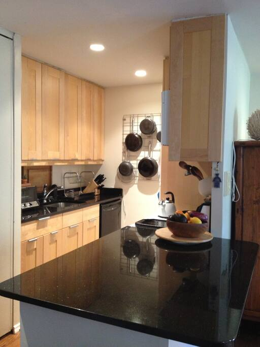 open, fully stocked, renovated kitchen with large, granite countertop and stools.