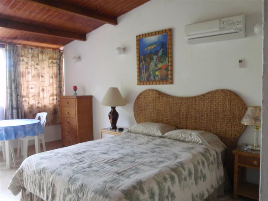 Air conditioned master bedroom with queen bed, sitting area, document safe and private bath.