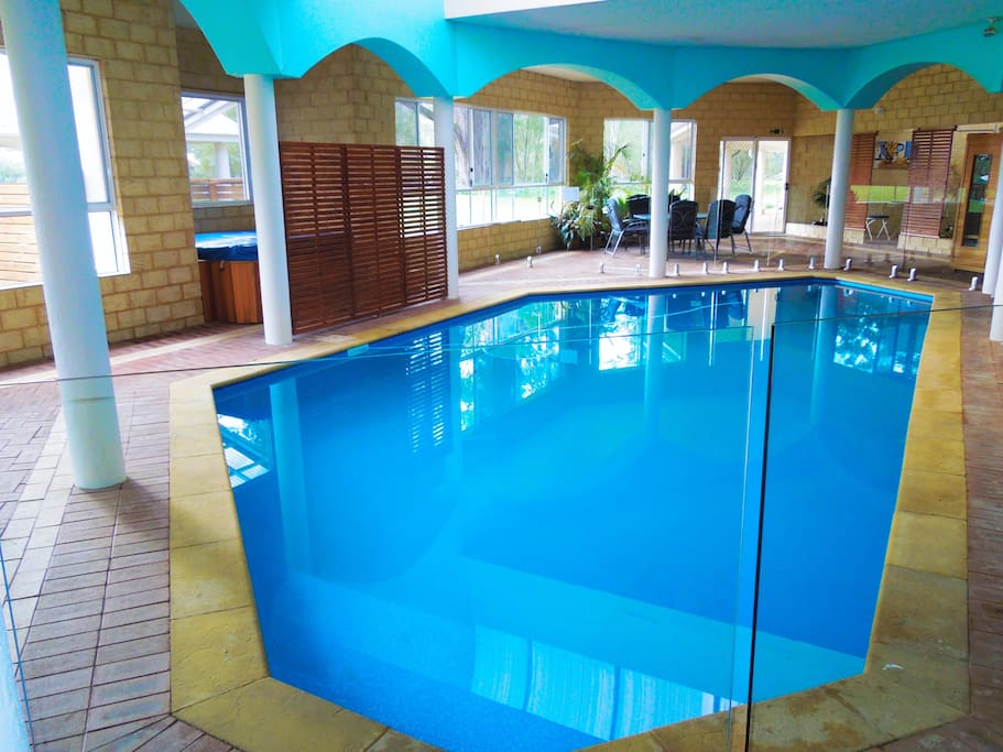 Spacious indoor entertainment area with pool, heated Jacuzzi, sauna, hooded BBQ, tables and chairs, plates, cutlery etc.