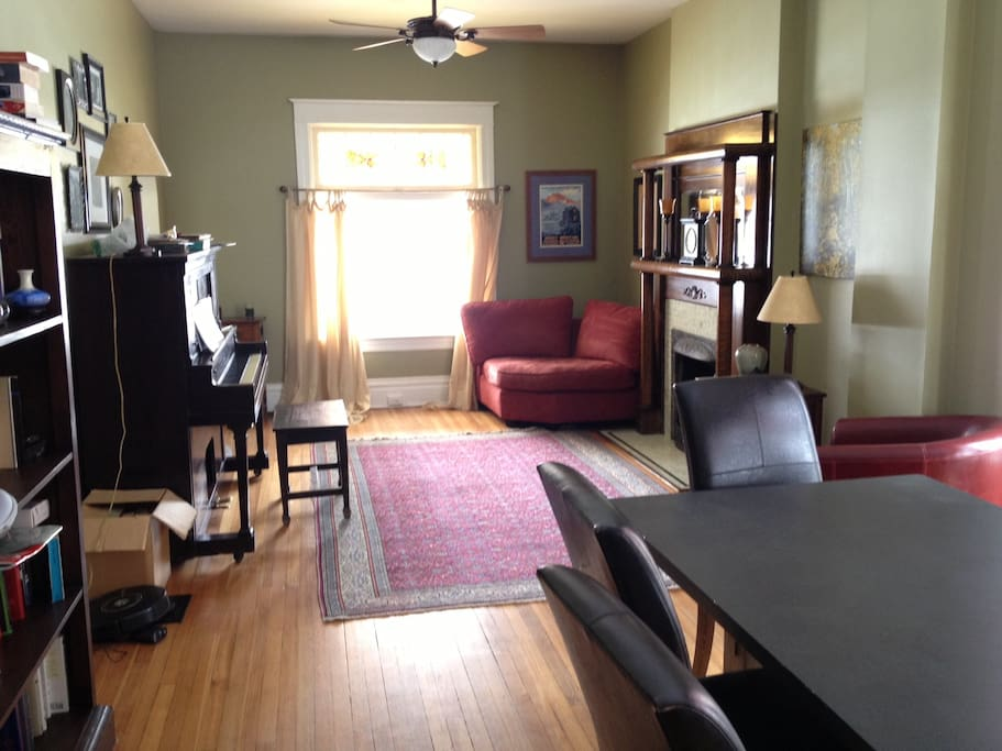 Front/Entry room on main floor with large dining room table and upright piano. Next to kitchen and office.