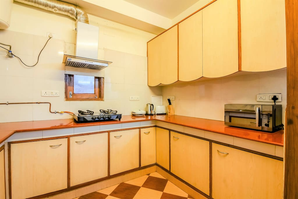 Fully loaded Kitchen with Stovetop Gas, Refrigerator, Microwave, Toaster, Kettle, Cookware & Cutlery to make a complete meal.
