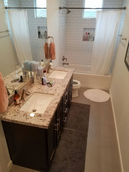 Large bathroom with double vanity and extra toiletries. Plenty of counterspace!