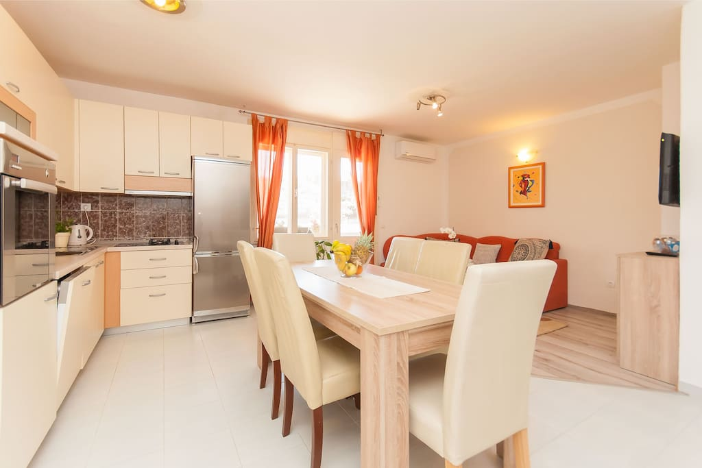 Large living dining table and a large fully equipped kitchen including a dishwasher.