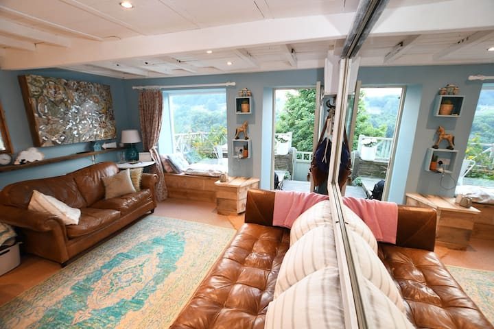 The picture window at the front is a great place to sit and admire the view, large mirrors reflect that view.  Our downstairs is open plan, with two comfy leather settees, relax after a walk Watch our 42 inch smart TV, curl up with Netflix.