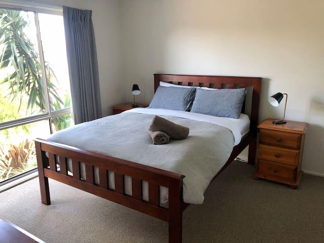 Bedroom 1: A queen bed with ensuite, walk in robe & smart TV